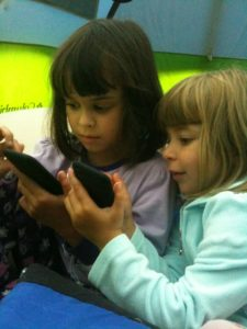 Photo of two children with devices